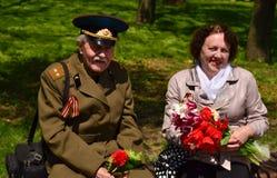 PYATIGORSK, RÚSSIA - 9 DE MAIO DE 2011: Os veteranos de Victory Day estão sentando-se em um banco com tulipas Fotografia de Stock