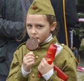 PYATIGORSK, RÚSSIA - 9 DE MAIO DE 2017: Menina em um forragem-tampão que come o gelado no feriado do 9 de maio foto de stock
