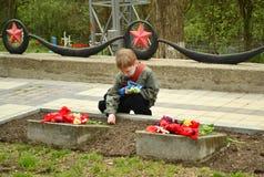 PYATIGORSK, RUSIA - 9 DE MAYO DE 2011: El muchacho pone las flores al monumento a los soldados caidos de la Segunda Guerra Mundia Foto de archivo