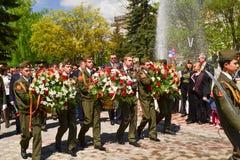 PYATIGORSK, RUSIA - 9 DE MAYO DE 2011: Las soldaduras militares ponen las flores al monumento al soldado caido Imágenes de archivo libres de regalías