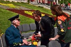 PYATIGORSK, RUSLAND - MEI 09, 2011: De hulp van vrijwilligersaanbiedingen aan een veteraan op Victory Day royalty-vrije stock foto's