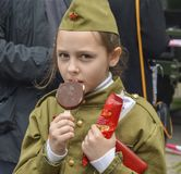 PYATIGORSK, RUSSIA - MAY 09, 2017: Girl in a forage-cap eating ice cream on the holiday of May 9 stock photo