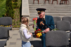 PYATIGORSK, RUSSIA - MAY 09, 2011: Girl gives flowers to veteran on Victory Day. Stock Photos