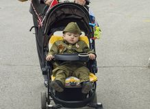 PYATIGORSK, RUSSIA - MAY 09, 2017: A little boy in uniform for the day of victory in baby stroller stock photography