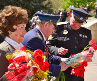 PYATIGORSK, RUSSIA - MAY 09, 2011: Woman and two military men with tulips on Victory Day. Stock Photos