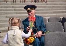 PYATIGORSK, RUSSLAND - 9. MAI 2011: Mädchen gibt dem Veteran auf Victory Day Blumen Lizenzfreie Stockfotos