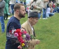 PYATIGORSK RYSSLAND - MAJ 09, 2017: den unga mannen stöttar en äldre man Arkivfoto