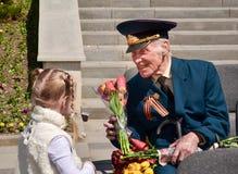 PYATIGORSK RYSSLAND - MAJ 09, 2011: Flickan ger blommor till veteran på Victory Day Fotografering för Bildbyråer