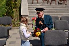 PYATIGORSK RYSSLAND - MAJ 09, 2011: Flickan ger blommor till veteran på Victory Day Arkivfoton