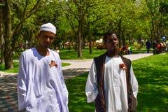 PYATIGORSK RYSSLAND - MAJ 09, 2011: Victory Day Afrikanska män är iklädda nationella dräkter och i solidaritet klämd fast St Geor Arkivfoto