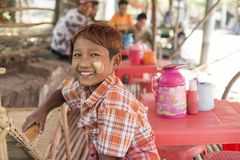 Young Burmese boy smiling. Pyay, Burma, February 2012: A smiley young Burmese boy with ginger hair and with the traditional thanaka decorations on his face Stock Images