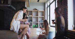 In pyjama's mooie dames die van de tijd genieten die thuis vrijgezellinpartij vieren die sommige toejuichingen van wijnglazen dri stock videobeelden