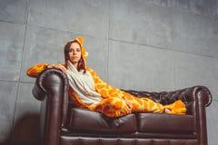 Pyjama's voor Halloween in de vorm van een giraf Emotioneel portret van een meisje op een bankachtergrond Gekke en grappige mens  stock afbeeldingen