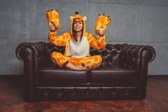 Pyjama's voor Halloween in de vorm van een giraf Emotioneel portret van een meisje op een bankachtergrond Gekke en grappige mens  royalty-vrije stock fotografie