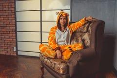 Pyjama's voor Halloween in de vorm van een giraf Emotioneel portret van een meisje op een bankachtergrond Gekke en grappige mens  royalty-vrije stock foto