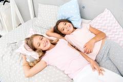 Pyjamapartei und -freundschaft Glückliche kleine Kinder der Schwestern, die im Schlafzimmer sich entspannen Freundschaft von klei lizenzfreie stockfotos