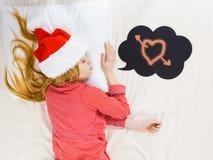 Pyjamas de femme de sommeil et chapeau de port de Santa Claus Photographie stock