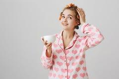 Pyjamas de port d'amie mignonne rêveuse avec des bigoudis d'impression et de cheveux de coeur, les touchant tout en souriant et t Image stock