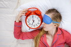 Pyjamas de port de femme de sommeil tenant l'horloge Photographie stock