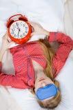 Pyjamas de port de femme de sommeil tenant l'horloge Photographie stock libre de droits