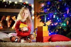Pyjamas de port heureux de Noël de petite fille jouant par une cheminée dans un salon foncé confortable le réveillon de Noël Photos libres de droits