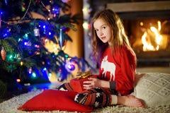 Pyjamas de port heureux de Noël de petite fille jouant par une cheminée dans un salon foncé confortable le réveillon de Noël Images stock