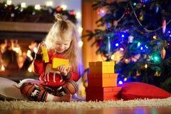 Pyjamas de port heureux de Noël de petite fille jouant par une cheminée dans un salon foncé confortable le réveillon de Noël Image libre de droits