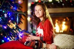 Pyjamas de port heureux de Noël de petite fille jouant par une cheminée dans un salon foncé confortable le réveillon de Noël Photo libre de droits