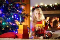 Pyjamas de port heureux de Noël de petite fille jouant par une cheminée dans un salon foncé confortable le réveillon de Noël Photos stock