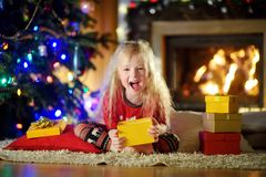 Pyjamas de port heureux de Noël de petite fille jouant par une cheminée dans un salon foncé confortable le réveillon de Noël Images libres de droits