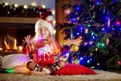 Pyjamas de port heureux de Noël de petite fille jouant par une cheminée dans un salon foncé confortable le réveillon de Noël Image stock