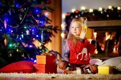 Pyjamas de port heureux de Noël de petite fille jouant par une cheminée dans un salon foncé confortable le réveillon de Noël Photographie stock