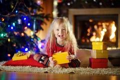 Pyjamas de port heureux de Noël de petite fille jouant par une cheminée dans un salon foncé confortable le réveillon de Noël Photo stock