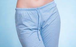 Pyjamas. Female legs wearing blue pajama pants Stock Image