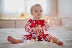 Pyjamas vestindo do bebê pequeno feliz que jogam com as decorações da árvore do ano novo fotografia de stock