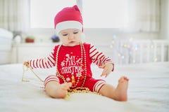 Pyjamas vestindo do bebê pequeno feliz que jogam com as decorações da árvore do ano novo fotos de stock