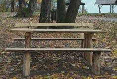 Pykniczny teren z drewnianymi ławkami i stołem po środku lasu Obrazy Royalty Free