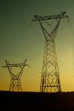 Pylônes électriques au coucher du soleil Photo stock