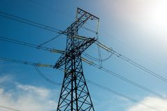 Pylônes d'une puissance de haute tension contre le ciel bleu Photographie stock