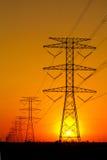 Pylônes de l'électricité contre le coucher du soleil Image stock