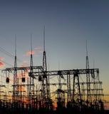 Pylône électrique de sous-station de distribution avec des lignes, au coucher du soleil Photo libre de droits