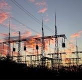 Pylône électrique de sous-station de distribution avec des lignes, au coucher du soleil Image libre de droits