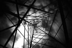Pylône de l'électricité avec des nuages se déplaçant en noir et blanc Photographie stock libre de droits
