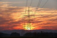 Pylône et lignes électriques au lever de soleil Images stock