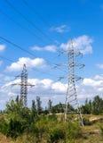 Pylône et lignes électriques de transmission de l'électricité dans une forêt Photographie stock libre de droits