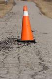 Pylône orange sur la route endommagée Photos libres de droits
