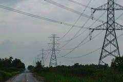 Pylônes à haute tension de puissance et la route Images libres de droits