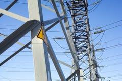 Pylônes de l'électricité avec le signe à haute tension d'avertissement Images stock