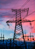 Pylônes et lignes de l'électricité au crépuscule au coucher du soleil Image stock