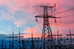 Pylônes et lignes de l'électricité au crépuscule au coucher du soleil Images libres de droits